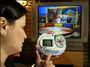 Kristen Connors, a toy demonstrator, becomes the fourth player in Hasbro's Wheel of Fortune, competing against actual players on TV's Wheel of Fortune game show. She played the game Feb. 13 in the company's showroom at the American International Toy Fair in New York. The game beams the puzzle from the TV directly to the hand-held unit.