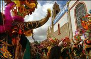 Devil dancers enter the Virgen del Socavon Church after doing a pilgrimage during carnival celebrations in Oruro, Bolivia. Thousands of dancers gathered Saturday in this mining city to pay homage to the Virgen del Socavon while performing dances on their pilgrimage to the virgin's chapel.