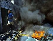 A university student runs past a fire on the streets of Port-au-Prince, Haiti. President Jean-Bertrand Aristide agreed Saturday to a U.S.-backed peace plan calling for shared power with political opponents, a new prime minister and fresh legislative elections.