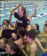 Members of Free State High's swimming and diving team hoist coach Annette McDonald after the Firebirds claimed the first state title in school history. FSHS won state Saturday at Kansas State Natatorium in Manhattan.