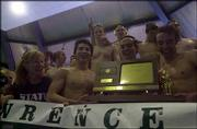 Free State High's boys team, including, front from left, coach Annette McDonald and senior co-captains Chris Wolff, Alex Brunfeldt and Will Hecht, displays its state swimming meet championship trophy. The Firebirds won the school's first state title Saturday in Manhattan.