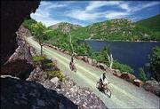 A pair of bicyclists glide past a vista overlooking Jordan Pond and the Bubbles Mountains on a carriage road at Acadia National Park, near Bar Harbor, Maine. The rocky, evergreen coast is perfect for those seeking an active, scenic vacation.