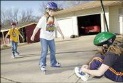 Korey Robinson, 9, far left, and Michele Peck, 8, skate while Kaley Robinson, 9, ties up her skating shoes. All three wore their helmets as they played on Friday. The city this week will consider an ordinance requiring youths under 15 to wear helmets while skating, cycling or riding a scooter.