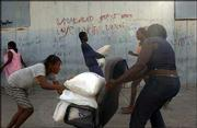 People carry away looted goods, including sacks of rice and flour, from the port of Cap-Haitien, Haiti. Rebels captured Haiti's second-largest city with little resistance Sunday, claiming Cap-Haitien as their biggest prize in a two-week uprising that has driven government forces from half the country.