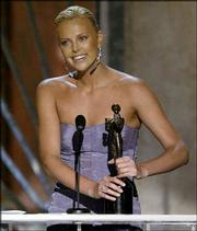 "Actress Charlize Theron accepts her award for best leading actress in a motion picture for her work in ""Monster"" at the Screen Actors Guild Awards on Sunday in Los Angeles."