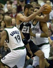 San Antonio forward Tim Duncan (21) splits the defense of Minnesota guard Sam Cassell (19) and center Michael Olowokandi, right, on his way to the basket. Duncan had 25 points as the Spurs beat the Timberwolves, 94-92, Sunday in Minneapolis.