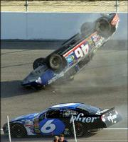 Carl Long's car (46) flips over as Mark Martin (6) drives past during the Subway 400 race. Long was not injured in the crash Sunday at North Carolina Speedway near Rockingham, N.C.
