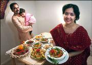 Bengali cooking is a specialty in the home of Saibal Bhattacharya, left, and his wife, Debjani Bhaduri, who produces a variety of foods for the Community Mercantile Co-op. Saibal holds their 23-month-old daughter, Sukanya, behind a table full of Indian dishes.