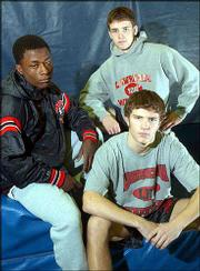Lawrence high wrestlers Pharouk Hussein, left, Brendan Halpin, top, and Nolan Kellerman lead the Lions into the state tournament this weekend in Wichita.