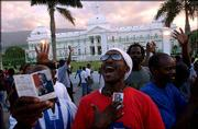 Loyalists of Haitian President Jean-Bertrand Aristide sing in his support in front of the National Palace in Port-au-Prince. Hundreds of Aristide supporters gathered Thursday in front of the palace and started building a defensive rampart.