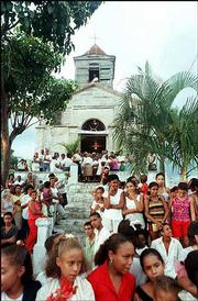 A long-standing embargo against Cuba -- imposed in the early 1960s after the communist government expropriated American companies and other property on the island -- is intended to punish President Fidel Castro's regime while showing support for the people of Cuba. Here, a crowd of Cubans surround a church.