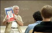 "Kansas University professor Bryant Freeman holds up Haitian President Jean Bertrand Aristide&squot;s political poster during a ""Contemporary Haiti"" course in Wescoe Hall. Freeman, who taught the class Thursday, has studied Haiti for more than 45 years."