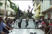 Rebel leader Louis-Jodel Chamblain sits atop a car, at right, after news of Haitian President Jean-Bertrand Aristide's departure reached northern Cap-Haitien.