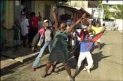 "Haitians celebrate, some shouting ""He&squot;s gone!,"" after news of President Jean-Bertrand Aristide&squot;s departure reaches northern Cap-Haitien, Haiti. Aristide on Sunday fled Haiti, bowing to pressure from a rebellion at home and governments abroad, U.S. and Haitian officials said."