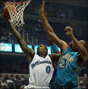 Washington's Gilbert Arenas (0) drives to the basket against New Orleans' Jamaal Magloire. Arenas scored 35 points in the Wizards' 111-106 overtime victory Monday in Washington.