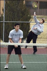 Jacob Gage serves the ball as Tommy Johnson waits for a return during the first day of tennis practice Monday at LHS.