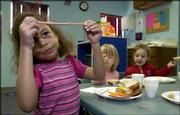 Sophia Walters, 5, plays with a piece of bologna as, from left, Caitlynn Grammer, 2 1/2, and Meadow Meier, 3, eat lunch. The trio ate Friday at the Brookcreek Learning Center annex at Lawrence High School. Under a proposal by Gov. Kathleen Sebelius, the center could receive additional funding from a state grant program called Smart Start.