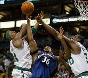 Boston's Paul Pierce, left, and Mark Blount, right, battle Washington's Etan Thomas. Pierce had 24 points, 10 rebounds and eight assists in the Celtics' 94-90 victory Friday night in Boston.