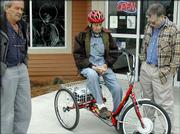 Dan Fogle Sr. learns about his new motorized tricycle from Gary Long, owner of Cycle Works, 2121 Kasold Drive. Fogle, 100, still lives on his own in Ottawa and recently failed an eye exam required to keep his driver's license. He plans to use the tricycle to run errands, including trips to the grocery store.