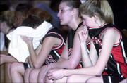 Lawrence High players, from left, Drew Huff, Megan Klingler and Sydney Wilson watch the waning moments of their loss to Overland Park Aquinas. The Saints defeated the Lions, 59-28, Friday night at Olathe South in the Class 6A sub-state final.
