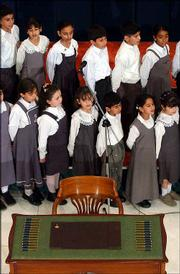 School children practice singing the Iraqi National Anthem behind a table with 25 pens and an empty chair lying idle in the middle of the lobby of the Convention Center for the historic new Iraqi interim Constitution in Baghdad, Iraq. The signing ceremony by the 25-member Iraqi Governing Council was delayed for more than five hours and then canceled after Shiite leaders refused to sign the interim constitution. Iraq's top Shiite cleric had rejected portions of the charter.