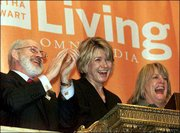 Martha Stewart, center, chairman and CEO of Martha Stewart Omnimedia, and company President and COO Sharon Patrick, right, are applauded by New York Stock Exchange President William Johnston as Stewart rings the opening bell Oct. 19, 1999.