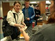 Kansas University freshman Rachel Smith, Dallas, buys a piece of pizza at the Kansas Union. Smith bought the food Tuesday, the same day KU announced it would merge its dining services so that food available at residence halls and the unions will be under control of the same department.