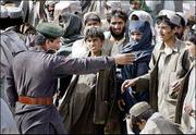 A Pakistani border guard directs people waiting at a border crossing in Spin Boldak, Afghanistan. Despite intense efforts by Pakistani, U.S. and Afghan military forces, Afghans insist that the border remains an open door for Taliban crossing into Afghanistan to carry out attacks.