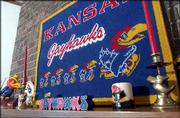 A mantel in the family room displays Jayhawk candles and candleholders under a KU rug.