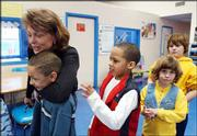 Boys and Girls Club director Janet Murphy hugs Keenan Vital, 8, as, from left, Brendon Maxey, 9, Rebekah Matt, 6, and Caitlyn Fannin, 10, follow behind. Murphy worked with the children Thursday at the club's headquarters, 1520 Haskell Ave.