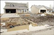 Bad weather has slowed home construction in Lawrence. Workers on a North Lawrence rooftop couldn't avoid the rain Monday but stayed clear of the mud puddles.