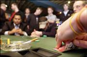 A poker player checks his hand before betting at the final table of poker night at Captain Ribman's Meat Market, 811 N.H. ThePokerPub, a Lawrence-based business, organizes Texas Hold'em poker games at five Lawrence bars and restaurants.