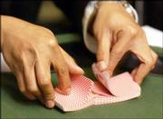 A dealer shuffles cards for the final table of the night's poker tournament.