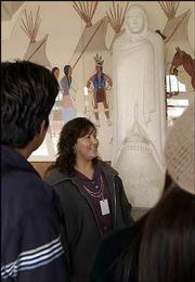 "Lori Tapahonso, a spokeswoman at Haskell Indian Nations University, talks with students about ""Comrade in Mourning,"" a two-ton marble sculpture by Allan Houser. The Haskell-commissioned sculpture, created in the 1940s and on display in the university&squot;s auditorium, will be part of the opening exhibit at the new National Museum of the American Indian in Washington, D.C."