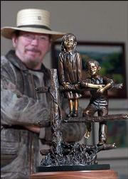"Lawrence sculptor Jim Brothers is the featured artist for the 2004 Lawrence Art Auction, set for April 24. Brothers is pictured with ""Promise,"" the bronze casting he donated for the auction."