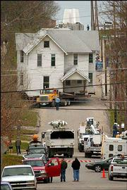 A 76-ton, 114-year-old house that used to call 1309 Ohio home is trucked down the steep incline of 13th Street, with the top of the Kansas University Campanile visible in the background. Workers with Valley Moving of Wamego moved the house Wednesday to 1033 Ky. The house's former site will be home to a new KU scholarship hall.