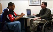 Kansas University junior men's basketball player Wayne Simien, left, laughs with academic counselor Scott Ward while going over Simien's homework schedule at Wagnon Student Athletic Center. Ward, who works with the men's basketball, volleyball and tennis squads at KU, has overcome a paralyzing accident to realize his dream of coaching.