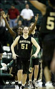 Baylor's Emily Niemann (51) rushes to meet teammate Dionne Brown, right, after beating Texas Tech in the Big 12 Conference tournament. Despite scandal surrounding the Baylor athletic department the women's basketball squad has thrived, advancing to the Sweet 16 of the NCAA Tournament.