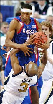 KU freshman J.R. Giddens, top, ties up Georgia Tech's Jarrett Jack. Giddens tied Keith Langford for team-high honors with 15 points.