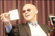 """James Carville shows his betting slip before his Monday speech at the Lied Center. Carville, co-host of CNN&squot;s """"Crossfire,"""" bet on the Kansas University men&squot;s basketball team to win its Sunday game."""