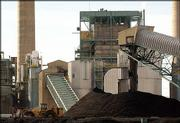 A front-end loader moves coal from a pile and toward a conveyor belt outside the coal-fired Cherokee Street power plant owned by Xcel Energy in north Denver. Triggered by the high cost of natural gas, utility companies are contemplating new, coal-fired electrical plants for the first time in more than a decade.