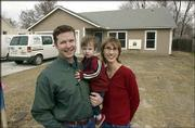Jeff and Shawna Huffman and their son Patrick, 2, stand outside their new very solid home on Locust Street.