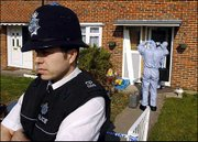 A police officer stands outside as forensic officers prepare to enter a house in Crawley, West Sussex, after raids across southeast England by six police forces. Eight men, all British citizens between the ages of 17 and 32, were arrested Tuesday under suspicion of being involved in terrorism. It was one of the biggest anti-terrorism operations in Britain since the Sept. 11, 2001, attacks in the United States, and a half-ton of ammonium nitrate, a cheap but effective bomb-making material, was found.