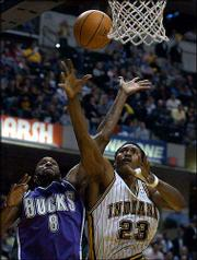 Indiana's Ron Artest, right, puts up a shot against Milwaukee's Joe Smith. Artest had 21 points and nine rebounds in the Pacers' 111-78 victory Wednesday night in Indianapolis.