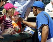 Royals manager Tony Pena, right, greets 5-year-old Katie Harrop as she waits for autographs next to her sister Kelly, 8, second from left, and her twin sister Ashley, far left. The young fans from Columbus, Ohio, visited Surprise, Ariz., Wednesday during their spring break.