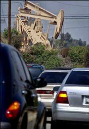 Traffic passes operating pumps at the Inglewood Oil Field in Los Angeles County. As Americans face high oil and gasoline prices, OPEC announced Wednesday that it would cut its crude oil production.