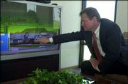 Joe Voth, president of Security Federal Mortgage Realty, points out aspects of a house on the company's big-screen TV. Customers can take virtual tours of houses posted on the Internet by watching the television. Security Federal Mortgage Realty formerly was a mortgage company but recently added real estate and insurance services.