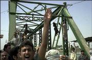 Iraqis chant anti-American slogans as charred bodies hang from a bridge over the Euphrates River in Fallujah, west of Baghdad. Enraged Iraqis killed four American contract workers Wednesday, took the charred bodies from a burning SUV, dragged them through the streets, and hung them from the bridge. In all, four U.S. civilians and five U.S. soldiers were killed in ambushes Wednesday in Iraq.