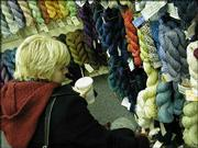 Genevieve Payne, of Lawrence, browses through racks of colorful twisted yarn at the Yarn Barn, 930 Mass. More and more young women -- and a few men -- are picking up the needles and learning to knit and purl.
