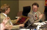 Newly installed mayor Mike Rundle, right, applauds outgoing mayor David Dunfield after presenting him with a gavel. Rundle took over as Lawrence mayor at Tuesday's City Commission meeting.